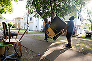 MILWAUKEE, WI — AUGUST 8, 2014: Rashad Yarbrough and Harry Woods with Eagle Moving and Storage Company removes a big screen TV from 4350 88th Avenue on the North Side of Milwaukee during a tenant eviction.