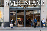 People with bags of shopping outside a branch of high street British fashion chain River Island in the city centre on 2nd September, 2021 in Leeds, United Kingdom. River Island is a high street fashion brand whose headquarters are in London, with branches all over the world.