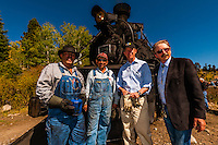 Hickenlooper with C&TSRR President John Bush and train crew<br />  aboard the Cumbres & Toltec Scenic Railroad train, during a visit riding from Antonito to Osier, Colorado. The Cumbres & Toltec Scenic Railroad has been jointly owned by the States of Colorado and New Mexico since 1970 when it was purchased from the Denver and Rio Grande Western Railway, which was going to scrap the line. The train makes a 64 mile run between Antonito, Colorado and Chama, New Mexico. The railroad is the highest and longest narrow gauge steam railroad in the United States with a track length of 64 miles. The train traverses the border between Colorado and New Mexico, crossing back and forth between the two states 11 times. The narrow gauge track is 3 feet wide. It runs over 10,015 ft (3,053 m) Cumbres Pass.