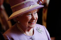 Queen Elizabeth II greets guests at a reception following Evensong in celebration of the centenary of the Order of the Companions of Honour at the Chapel Royal Hampton Court Palace in southwest London.