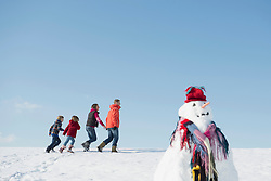 Family talking walk in winter, snowman in foreground, Bavaria, Germany