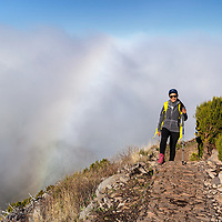 Pare, hiking on the top of Pico Ruivo, with a rainbow in the background.