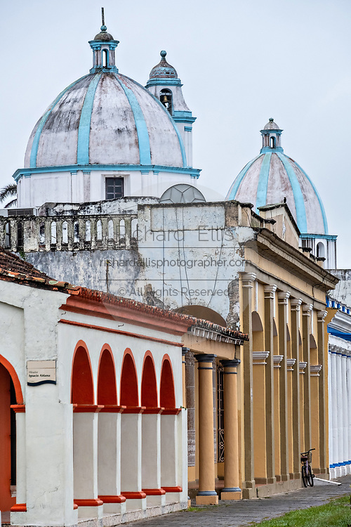 The domes of the Sanctuary of Our Lady of Candlemas church tower above the colorful colonnade style buildings in Tlacotalpan, Veracruz, Mexico. The tiny town is painted a riot of colors and features well preserved colonial Caribbean architectural style dating from the mid-16th-century.