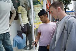 Two teenaged boys looking in a shop window,
