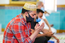 © Licensed to London News Pictures. 20/07/2020. London, UK. Muslim worshippers perform first prayer at Wightman Road Mosque, also known as London Islamic Cultural Society and Mosque, in north London as the Mosque reopens for Zuhr (the afternoon prayer) after almost four months of lockdown. Last month the government announced that gatherings of more than 30 worshippers are allowed for acts of communal worship in churches, synagogues, mosques, temples and other places of worship. All worshippers attending Mosques have to wear face coverings and bring their own prayer mat, Quran, and a reusable shoe bag. Photo credit: Dinendra Haria/LNP