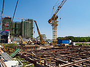 """15 FEBRUARY 2019 - SIHANOUKVILLE, CAMBODIA: The foundation being laid for La Tree, a Chinese development in Sihanoukville, with another Chinese casino under construction behind it. There are about 80 Chinese casinos and resort hotels open in Sihanoukville and dozens more under construction. The casinos are changing the city, once a sleepy port on Southeast Asia's """"backpacker trail"""" into a booming city. The change is coming with a cost though. Many Cambodian residents of Sihanoukville  have lost their homes to make way for the casinos and the jobs are going to Chinese workers, brought in to build casinos and work in the casinos.     PHOTO BY JACK KURTZ"""