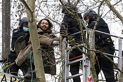 Steeple Claydon, UK. 24 February, 2021. Thames Valley Police officers acting on behalf of HS2 Ltd use a cherry picker to attempt to evict an activist opposed to the HS2 high-speed rail link from ancient woodland known as Poors Piece. Thames Valley Police stepped in to replace National Eviction Team bailiffs. The activists created the Poors Piece Conservation Project in the woodland in spring 2020 after having been invited to stay on the land by its owner, farmer Clive Higgins.