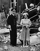 King George V and Queen Elizabeth, stand in the ruins of Buckingham Palace after an air raid in World War II
