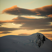 The moon rises over a rocky mountain range in Paradise Harbor, Antarctica, while the setting sun casts a golden glow on the clouds and sky.