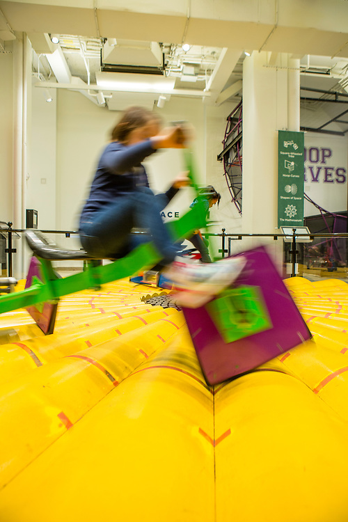 Children ride square-wheeled tricycles at the National Museum of Mathematics. Because of the surface of the track, the ride is smooth despite the square wheels.