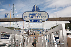 United States, Washington, San Juan Island, Friday Harbor. boy wheeling suitcase up ramp at the Port of Friday Harbor.  MR