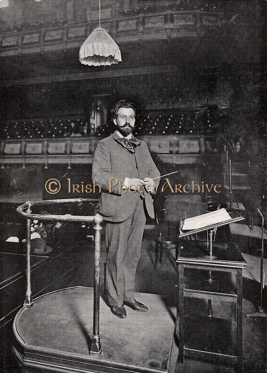 Henry Joseph Wood (1869-1944) English conductor. Wood on the conductor's podium at the Queen's Hall, London, in 1903.  In 1895 he took charge of the Promenade concerts at Queen's Hall and continued in this role for the next 50 years.  After the destruction of Queen's Hall in the London blitz in 1941 the season of Promenade concerts transferred to the Royal Albert Hall, Kensington, where they still continue.