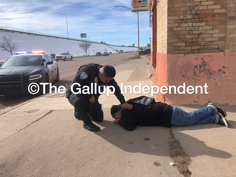 A Gallup Police officer checks on a man who identified himself as Brain Charley at the corner of Maloney Avenue and Fourth Street in Gallup Jan. 4.