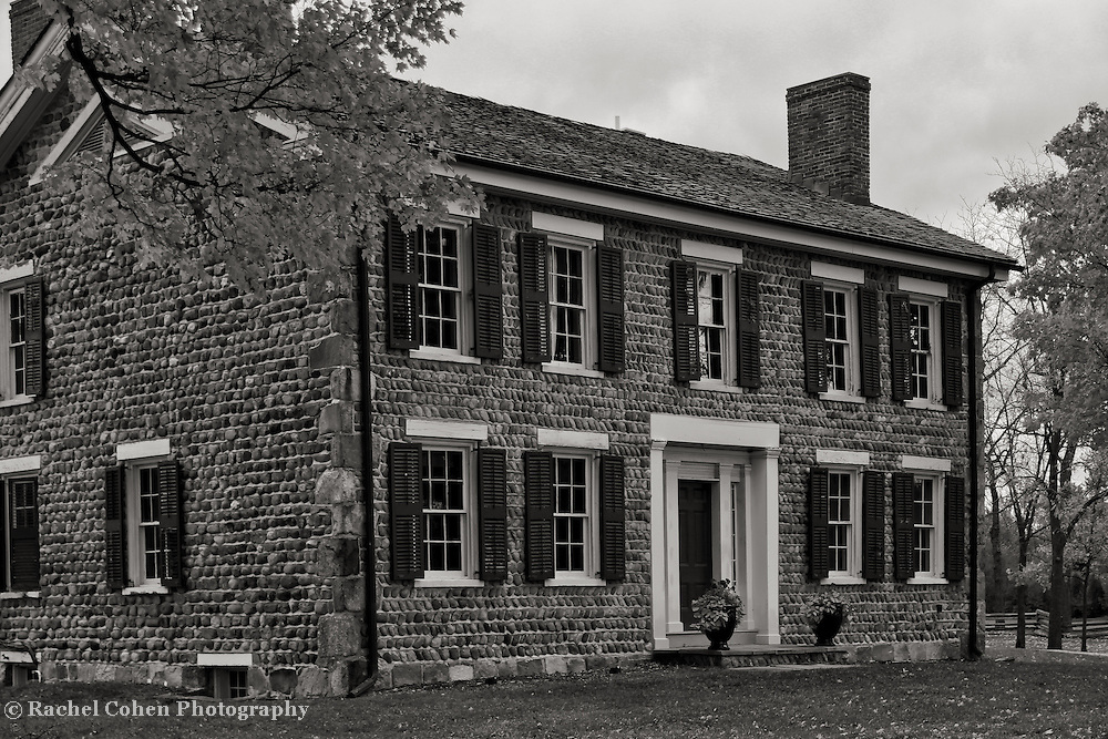 """""""Cobblestone Farm Beauty"""" B&W<br /> <br /> Cobblestone Farm is a beautiful historic home and farm located in Ann Arbor Michigan. The lovely stone work on this home is gorgeous anytime of the year, and in color or black and white. This scene is set in autumn with Maple trees surrounding it with their foliage!!<br /> <br /> Black and White images by Rachel Cohen"""