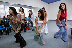Maria Teresa Torres teaches teenage girls how to pose for a photographer as part of a 6 month course at Giselles, one of Caracas' most famous modeling academies.  Modeling academies and beauty schools are essentially used as finishing schools in Venezuela.  Girls take classes in runway walking, photo shoots, oratory, makeup and hair.  The same qualities that are associated with beauty queens and models are thought to define a proper woman in much of Venezuela.
