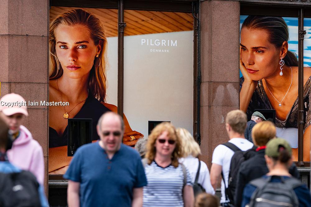 Edinburgh, Scotland, UK. 24 July, 2020. Shoppers on Princes Street waIk past window display for Pilgrim of Denmark, in Jenners department store.  Iain Masterton/Alamy Live News
