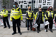 Climate justice is migrant justice protesters dressed as a 'Hostile Environment Border Force' chained together at an Extinction Rebellion demonstration gathering outside the Home Office in solidarity with migrants and those who suffer because of migration systems wordwide on 4th September 2020 in London, United Kingdom. With government resitting after summer recess, the climate action group has organised two weeks of events, protest and disruption across the capital. Extinction Rebellion is a climate change group started in 2018 and has gained a huge following of people committed to peaceful protests. These protests are highlighting that the government is not doing enough to avoid catastrophic climate change and to demand the government take radical action to save the planet.