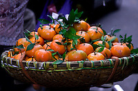 A basket of oranges on the back of a bicycle.