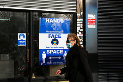 © Licensed to London News Pictures. 15/12/2020. London, UK. A woman wearing a face covering walks past a poster displayed in a shop window in north London which has closed following the outbreak of COVID19 and the lockdowns in the UK. According to The Office for National Statistics, the UK unemployment rate rose to 4.9% in the three months to October, with up to 1.7 million people out of work. The hospitality sector has been affected by coronavirus lockdowns and restrictions, and a number of workers have lost their jobs. London moves to Tier Three from midnight, when pubs, restaurants, bars, and cafes will only provide a take away service. Photo credit: Dinendra Haria/LNP