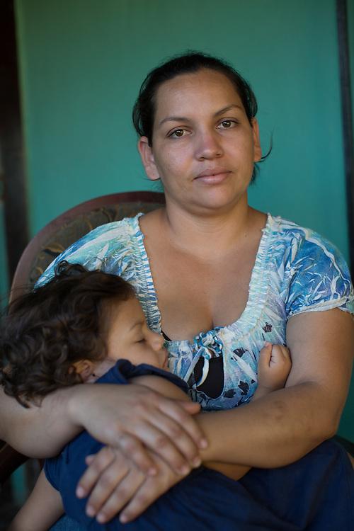 Cocinera en Catacamas. Dina Escoba, 28 y Alan Mejía Verbinsky y su bebé Alejandra. <br /> <br /> Fuimos deportados de la frontera Mexico y los Estados Unidos. Fue horrible, no queremos volver a pasar por eso, tenemos suerte de estar aquí contando la historia, gracias a Dios. Hemos tomado la decisión de no volver a intentar nunca. Miramos gente que cayó del tren, que fue llevada. A muchos los llevan y desaparecen, muchos son robados, violadas, golpeados, a muchos les piden un rescate, y allí esta todo perdido. Así es la vida allí. Desde que sale uno de la frontera de Honduras a Guatemala, ya a uno lo extorsionan, hasta la policía le quitan el dinero. Es difícil. <br /> <br /> Yo intenté una vez, mi esposo intentó varias veces. Viajamos por semanas, y cuando llegamos al río, ya para cruzar el río, nos agarró la migración, nos pusieron esposas y nos subieron a un camión y nos llevaron. Nos llevaron a Monterey, y nos pusieron en una cárcel, pero no una cárcel de migración, una cárcel normal, y estuvimos 23 días porque no se podía llenar un bus para mandarnos hasta DF para ver la gente de migración. Después nos mandaron para DF, y después para Tapachula, y de Tapachula para la frontera de Honduras con Guatemala. Fuimos tratados como criminales.<br /> <br /> Al llegar aquí no teníamos nada. No teníamos trabajo, mi esposo conseguía trabajo un día sí un día no, así pasábamos, pero la mayoría del tiempo haciendo nada. Y, gracias a Dios, nos hablaron de la Federación, y nos visitaron, incluso no creíamos, de allí nos hablaron que fueramos a Juticalpa a la reunión, y fuimos y miramos que la cosa era en serio. Desde que nos involucramos nos hemos perdido una reunión. Y gracias a Dios estamos trabajando. El negocio de nosotros, que hemos levantado con el apoyo de la Federación, es golosinas. Vendemos tacos, baleadas, plátanos con carne, tajaditas con pollo, y, gracias a Dios, desde que empezamos, todo producto que preparamos se vende, se nos va todo. Empezó con solamente