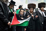 Ultra-Orthodox anti-Zionist Haredi Jews from Neturei Karta UK stand holding a Palestinian flag during the National Demonstration for Palestine on 22nd May 2021 in London, United Kingdom. The demonstration was organised by pro-Palestinian solidarity groups in protest against Israels recent attacks on Gaza, its incursions at the Al-Aqsa mosque and its attempts to forcibly displace Palestinian families from the Sheikh Jarrah neighbourhood of East Jerusalem.