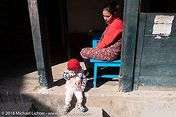 Nepalese woman with her baby on the main street of Tatopani on Day-7 of our Himalayan Heroes adventure riding from Tatopani to Pokhara, Nepal. Monday, November 12, 2018. Photography ©2018 Michael Lichter.