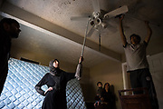 Kawthar Alsaloum (second from L), 23, helps brother-in-law Mohammed Alsaloum (right), 21, clean a fan while moving into a temporary apartment in Tampa, Florida, U.S. The space served as a temporary home for the Alsaloum family and got them out of the Days Inn, until the resettlement agency could find a more suitable longterm living situation.
