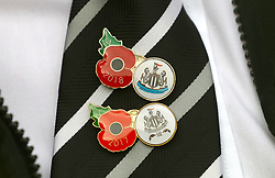 Detail of a Newcastle United fan wearing a Armistice Day pin badge ahead of the Premier League match at St James' Park, Newcastle.