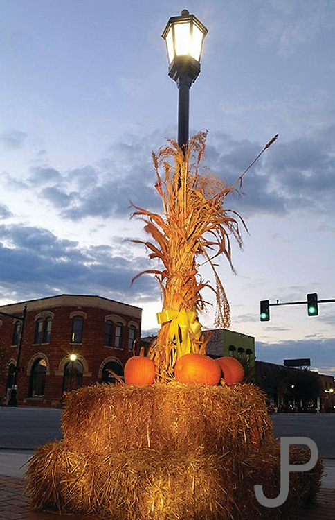 Sunset view of downtown Edmond, Oklahoma with pumkins and corn stalks.