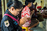 31 OCTOBER 2012 - YARANG, PATTANI, THAILAND: A woman in the Thai Army prays with villagers in Wat Kohwai before they left on a procession to Yala for Ok Phansa. Ok Phansa marks the end of the Buddhist 'Lent' and falls on the full moon of the eleventh lunar month (October). It's a day of joyful celebration and merit-making. For the members of Wat Kohwai, in Yarang District of Pattani, it was a even more special because it was the first time in eight years they've been able to celebrate Ok Phansa. The Buddhist community is surrounded by Muslim villages and it's been too dangerous to hold the boisterous celebration because of the Muslim insurgency that is very active in this area. This the year the Thai army sent a special group of soldiers to secure the village and accompany the villagers on their procession to Yala, a city  about 20 miles away.   PHOTO BY JACK KURTZ