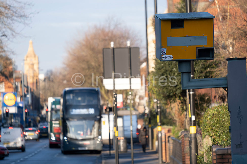Vehicles approaching a yellow speed camera in Wake Green on 7th January 2021 in Birmingham, United Kingdom. A traffic enforcement camera is a camera which may be mounted beside or over a road or installed in an enforcement vehicle to detect traffic regulation violations, including speeding.
