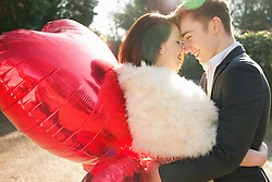 Young Couple Embracing Holding Heart Shaped Balloons