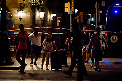 August 17, 2017 - Barcelona, Catalonia, Spain - Tourists are guided by a police officer in Las Ramblas area of Barcelona where there has been a terrorist attack. Thirteen people are dead and at least 50 injured after a van rammed into the crowd of Las Ramblas  street in Barcelona. (Credit Image: © Jordi Boixareu via ZUMA Wire)