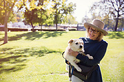 Mature woman holding dog in park