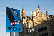 A Brexit placard outside Houses of Parliament, showing a smartly dressed person holding a gun to a shoe in the Union Jack colours, on the 13th December 2018 in Central London in the United Kingdom.