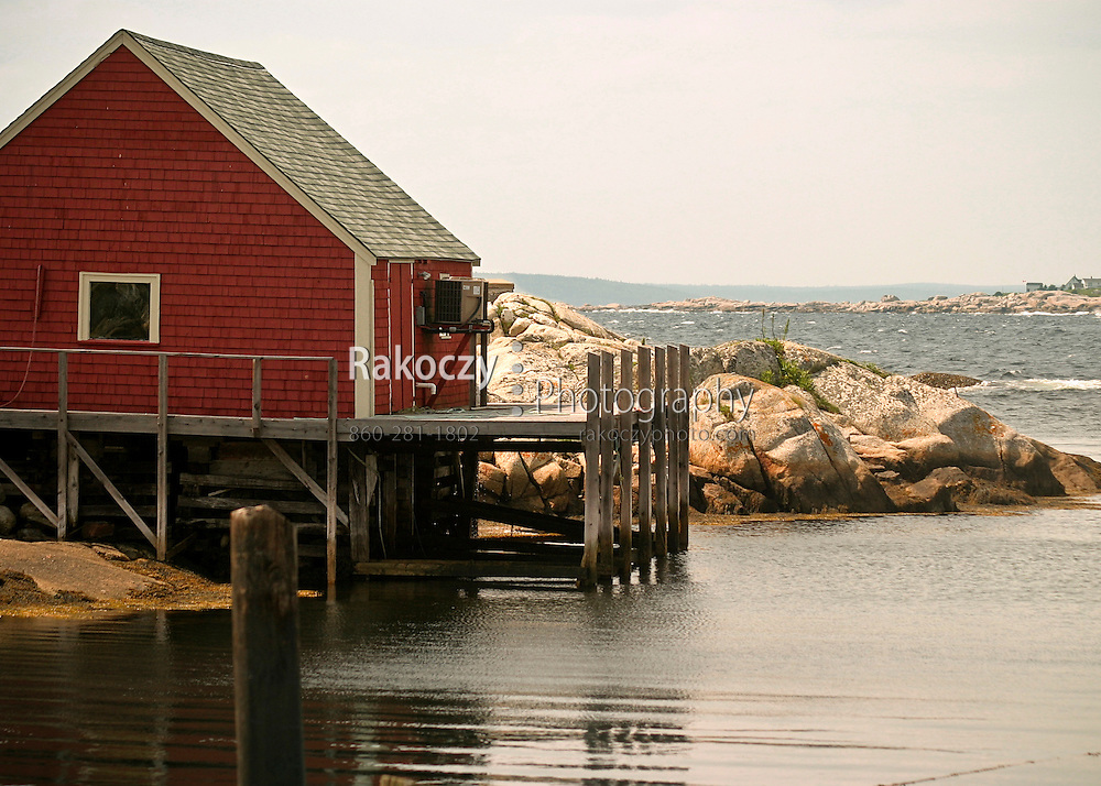 A rustic red house and it's dock stand over the cold waters of Peggy's Cove in Nova Scotia, Canada.