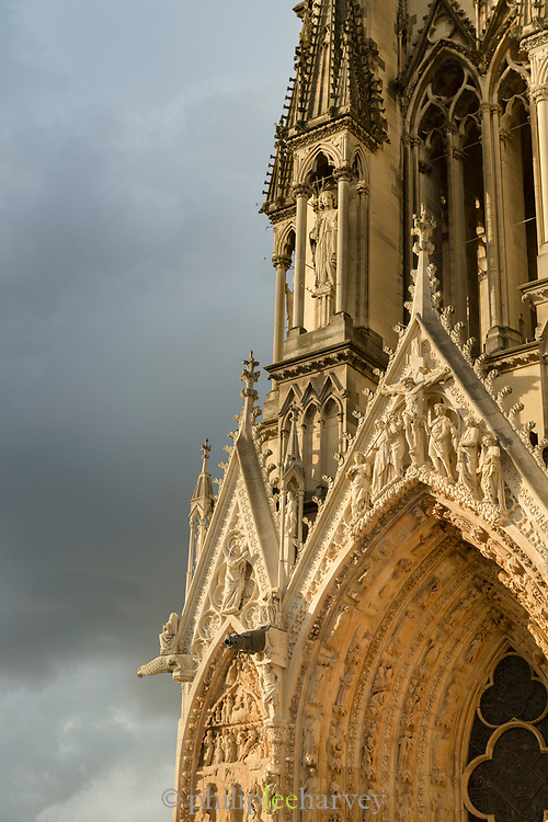Architectural details of Cathedral of Notre-Dame with cloudy sky in background, Reims, France