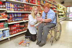Man; who is wheelchair user; shopping in supermarket with assistance of teenage carer,