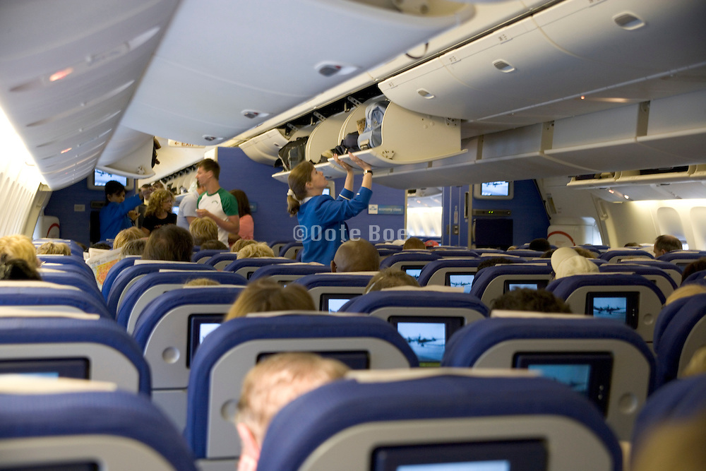 KLM stewardess closing overhead storing compartment