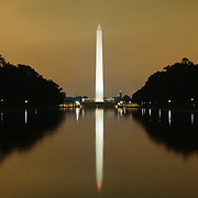Washington Monument reflected on the Reflecting Pool, with orange glow of city lights off low clouds