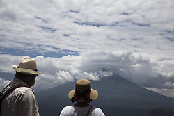 October 3, 2017 - Bali, Bali, Indonesia - Bali, Indonesia, 03 October 2017 :Two tourist from Russia watching the beautiful of mount agung from a temple site.  Mount Agung statust still on level warning and people on the danger zone were still on refugee save place. It still uncertain of Moung Agung will erupt. (Credit Image: © Donal Husni via ZUMA Wire)