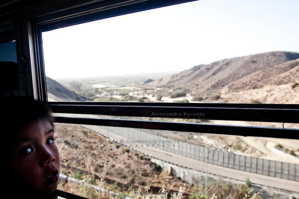 Tijuana 2015.<br /> A young boy in Tijuana, watching the border from the schoolbus.<br /> <br /> Un bambino, tornando da scuola, guarda la frontiera dal finestrino dell'autobus.