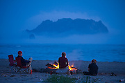 Campers sit by a campfire on the beach at Norwegian Memorial, Olympic National Park North Coast, Washington.