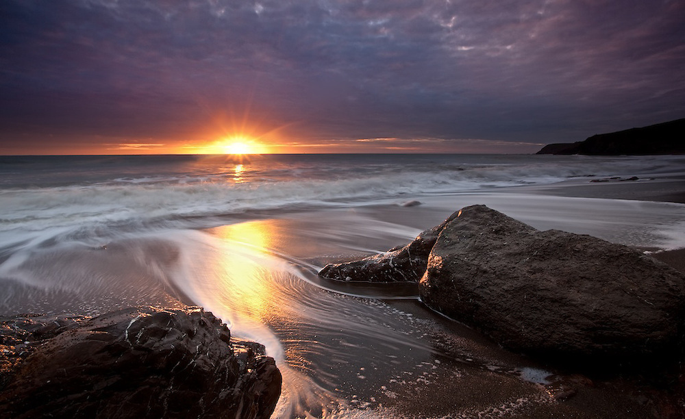 storm breaking right at sunset on rodeo beach in the marin headlands of northern california.