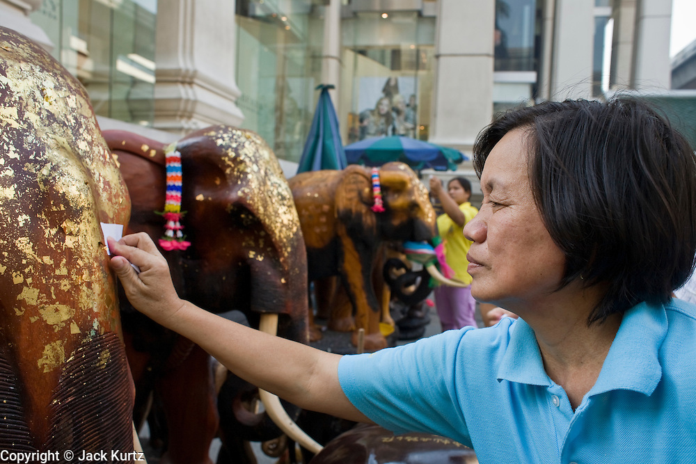29 FEBRUARY 2008 -- BANGKOK, THAILAND:  A woman rubs gold leaf on an elephant statue at the Erawan Shrine in Bangkok, Thailand. The Erawan Shrine is a Hindu shrine in Bangkok that houses a statue of Phra Phrom, the Thai representation of the Hindu creation god Brahma. A popular tourist attraction, it often features performances by resident Thai dance troupes, who are hired by worshippers in return for seeing their prayers at the shrine answered. The Erawan Shrine was built in 1956 as part of the government-owned Erawan Hotel to correct bad omens believed to be caused by laying the foundations on the wrong date.   Photo by Jack Kurtz