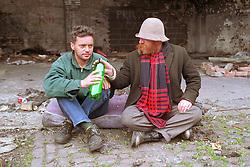 Two homeless men sharing bottle of cider in street,