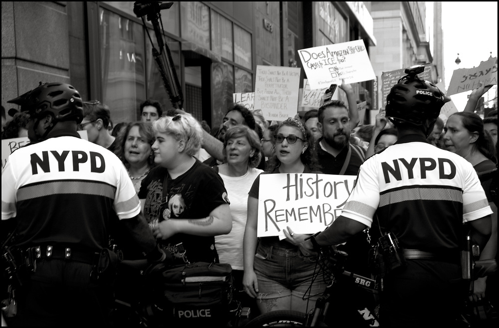 """On August 11, 2019, in New York City, more than 1,000 demonstrators crammed into an Amazon store to protest Amazon's contract with ICE, which uses Amazon technology.<br /> <br /> The protest, organized by a new group called Never Again Action, was designed to draw explicit links between the Holocaust and the treatment of undocumented immigrants today across the country.<br /> <br /> The protesters held a large sign that read """"Never again means never again"""" and, with most of the protesters sitting on the floor of the store, read accounts of people detained in immigration facilities. Over 40 demonstrators were arrested."""