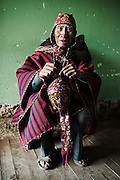 An elderly man, following the Andean tradition, weaves himself a new hat from alpaca wool at the textile market in Chinchero, Peru on September 11, 2005.