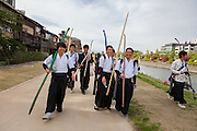 School boys carrying archery equipment, walk along the sides of the Kamo River in Gion, Kyoto, Japan. Sunday April 24th 2016