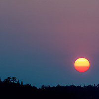 Tinted by smoke from distant forest fires, the sun sets over Lake of the Woods in Ontario, Canada.